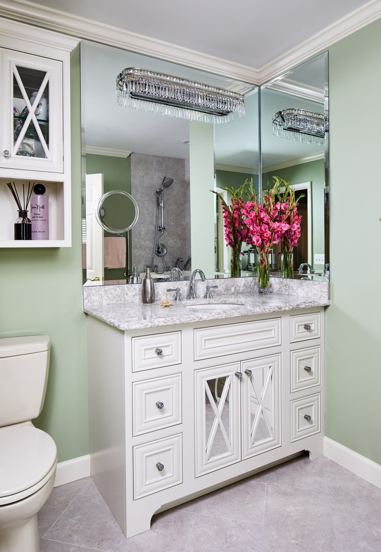 bathroom vanity with square mirror with crystal light fixture and small toilet above two glass doors