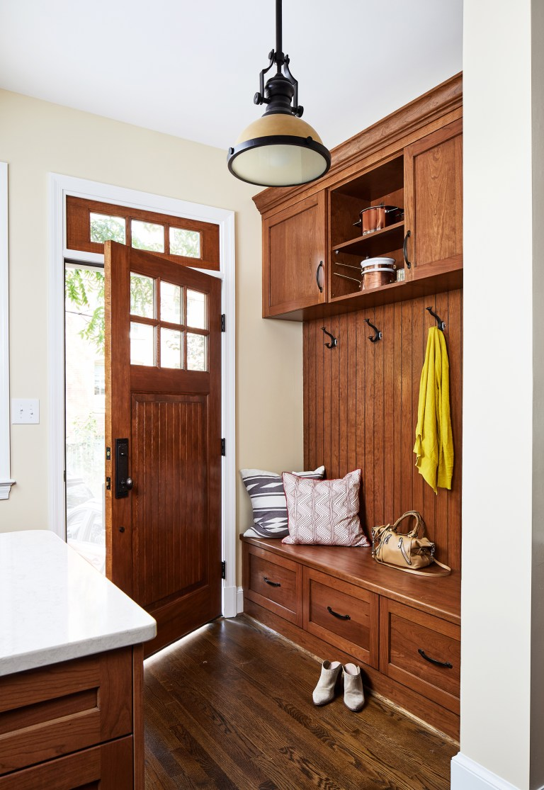 wood mudroom lockers bench and coat rack with a couple of storage drawers and wood hard floors
