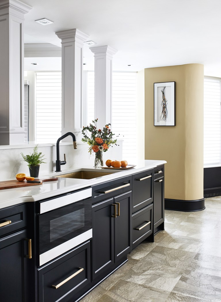 gold kitchen farmhouse sink and black mount pull down faucet with black and gold hidden behind cabinet panels