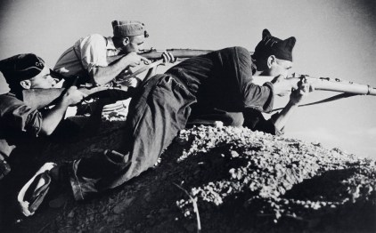 SPAIN. Cordoba front. Early September, 1936. Three Loyalist militiamen in a gully aiming rifles.