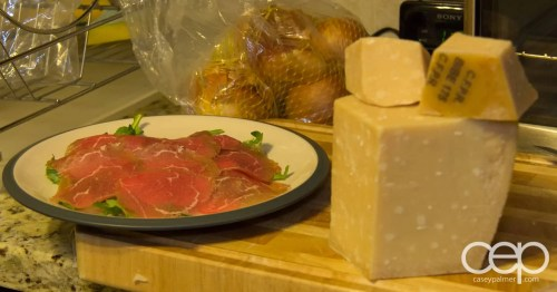 A plate of beef carpaccio and arugula with a block of parmigiano cheese ready to go!