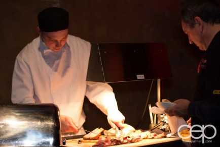Catering staff slicing some beef at the carving table