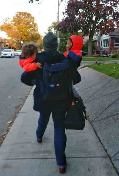 A photo of Casey carrying his two sons down the street, November 2017