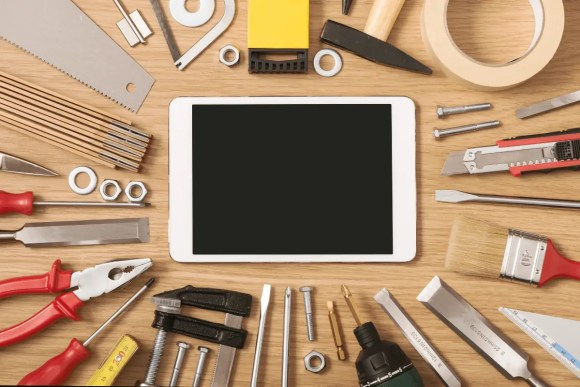 SEO tools: An overhead picture of an iPad surrounded by traditional tools on a tabletop.