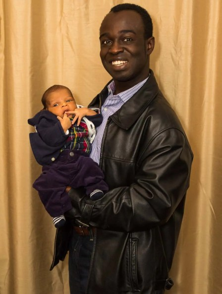 A photo of Casey holding his eldest son at twenty days old in his dining room.