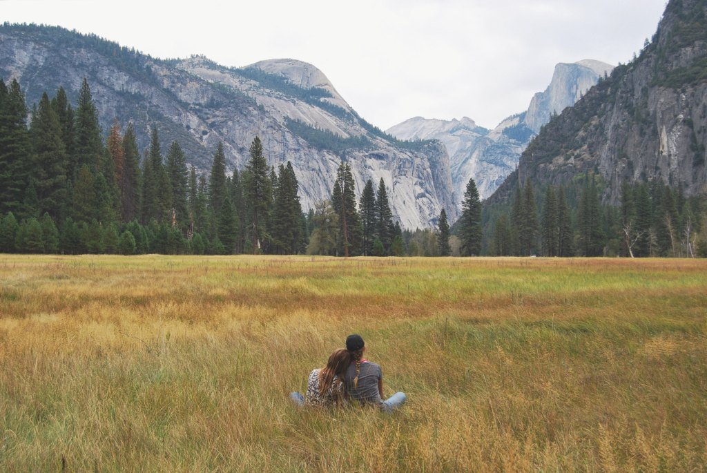 Couple sitting at the foothills of mountains.
