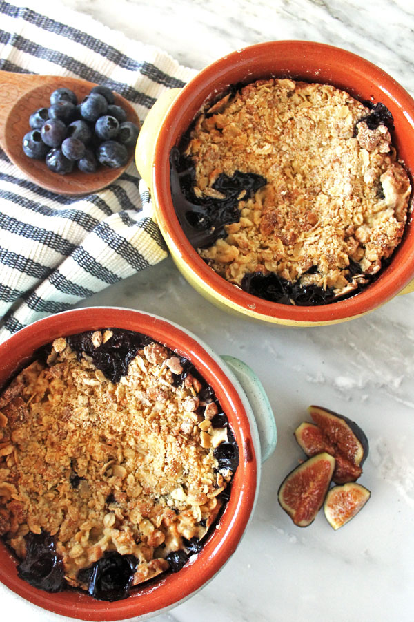 Two bowls of fig and blueberry cobbler with fresh cut figs and a spoonful of blueberries