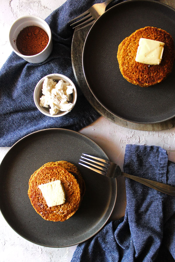 Two plates of stacked pumpkin pancakes topped with vegan butter.