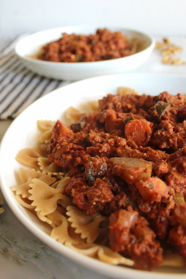 "Two bowls on walnut and tofu ""meat"" bolognese sauce in white bowls."