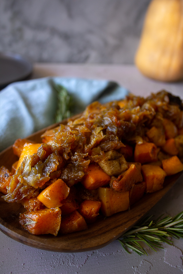 Roasted apple and butternut squash with caramelized onions on a wooden platter with plate, rosemary, and butternut squash in the background.