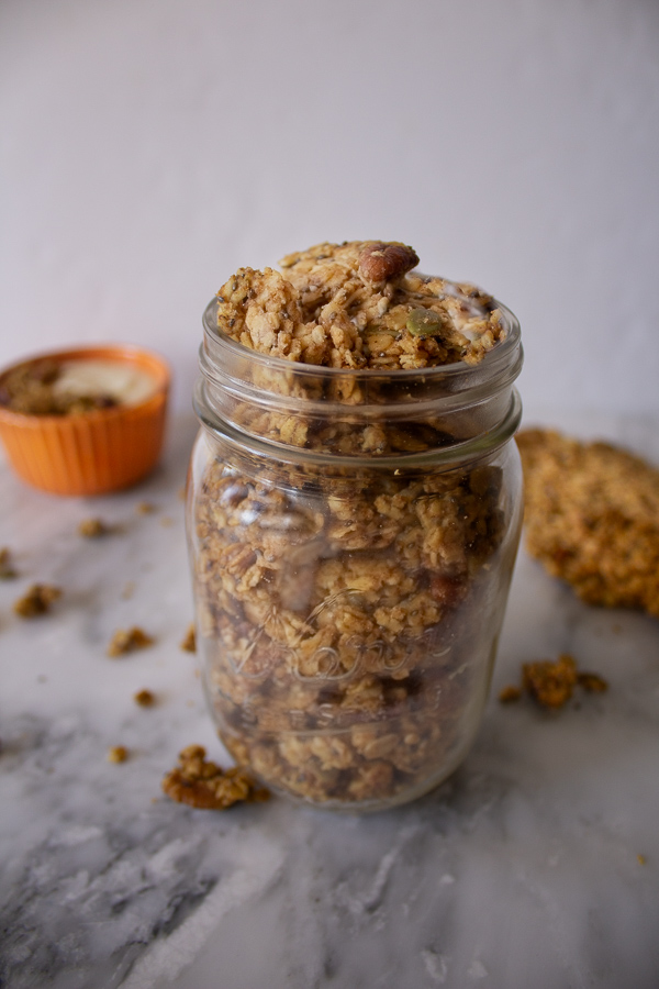 A jar of pumpkin pie granola with oat yogurt in an orange bowl topped with pumpkin pie granola in the background.