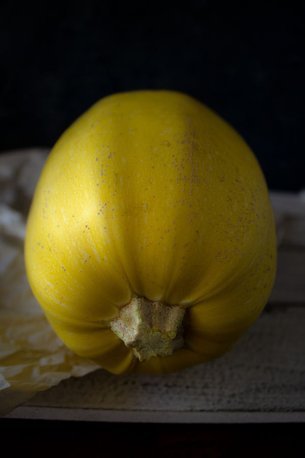 Close up photo of a spaghetti squash on a wooden table with a black background.
