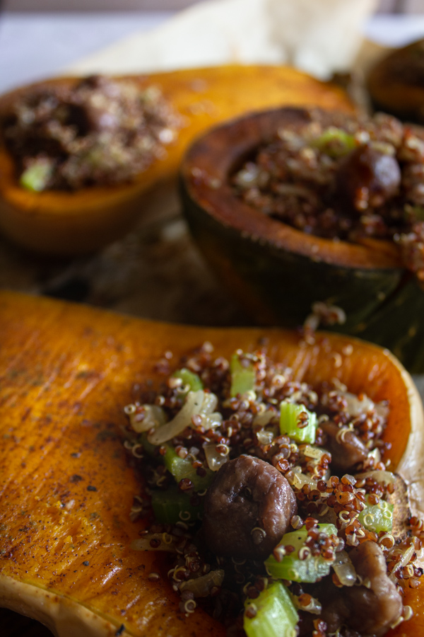 Quinoa and chestnut dressing inside a roasted butternut squash with more stuffed squash in the background.