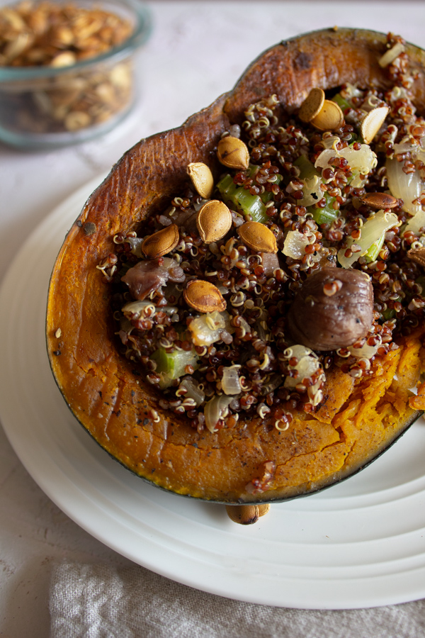 Quinoa and chestnut dressing stuffed kabocha squash on a plate with roasted squash seeds in the background.