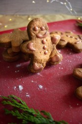 Gingerbread man cookie resting on a red cutting board surrounded by more gingerbread men cookies.