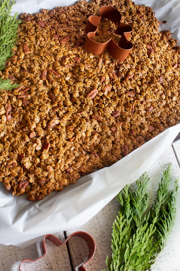 Gingerbread granola on a sheet pan surrounded by pine and gingerbread cookie cutters.