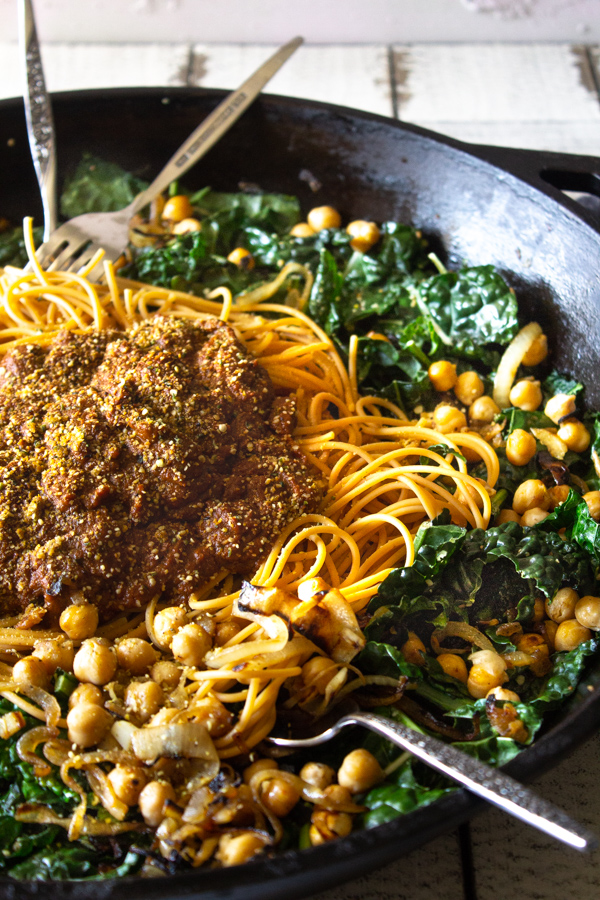 Pumpkin spaghetti with caramelized onions, chickpeas and garlic kale in a large cast iron skillet with forks and spoons digging in.