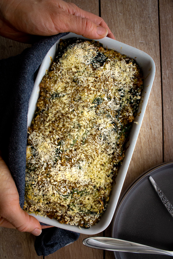 A loaf pan of quinoa spinach bake wrapped in a blue kitchen towel being placed on the table.