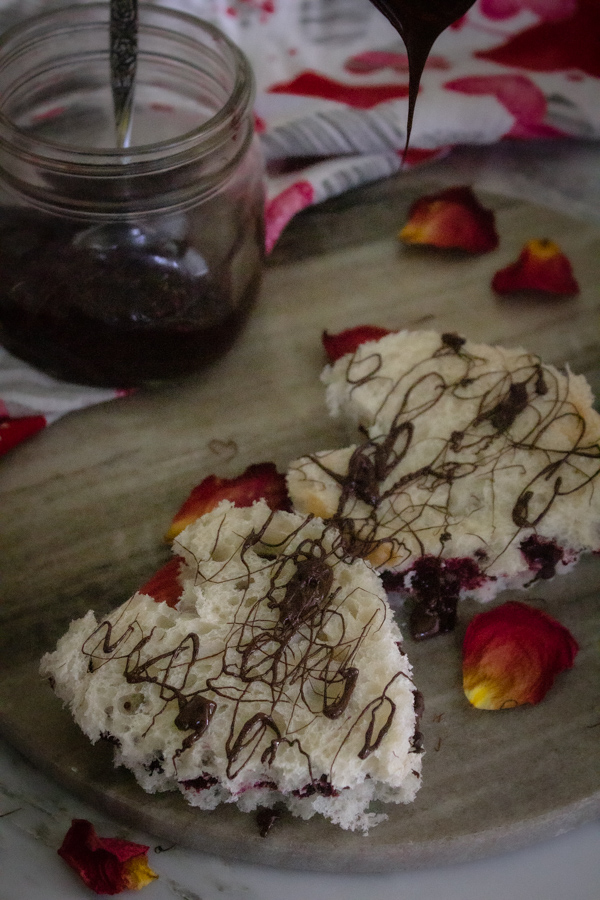 Berry jam and chocolate sauce heart sandwiches being drizzled with chocolate sauce on a bed of rose petals.