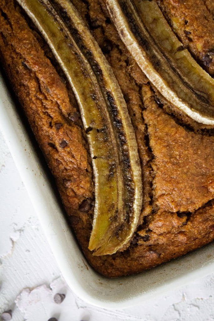 A loaf of chocolate peanut butter banana bread with sliced banana on top.