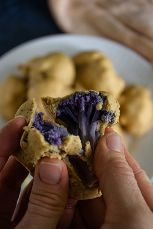 Hands holding a split open Nashville hot cauliflower wing revealing a purple cauliflower floret with more cauliflower on a white plate in the background.