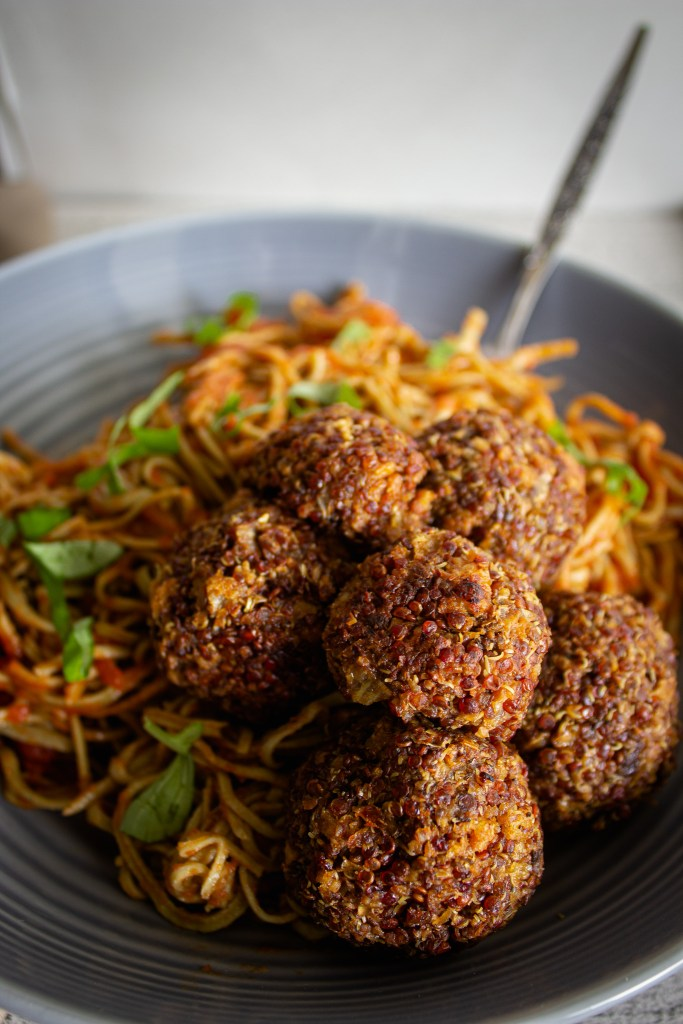 Bowl of vegan no meatballs with spaghetti and fresh basil strands.
