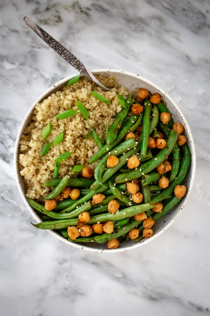 A bowl of pan-cooked chickpeas and green beans on a bed of quinoa and topped with green onions and sesame seeds in a white bowl.
