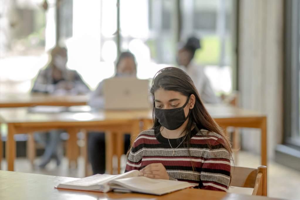 106817596 1609352309642 Hispanic college student wearing mask while studying
