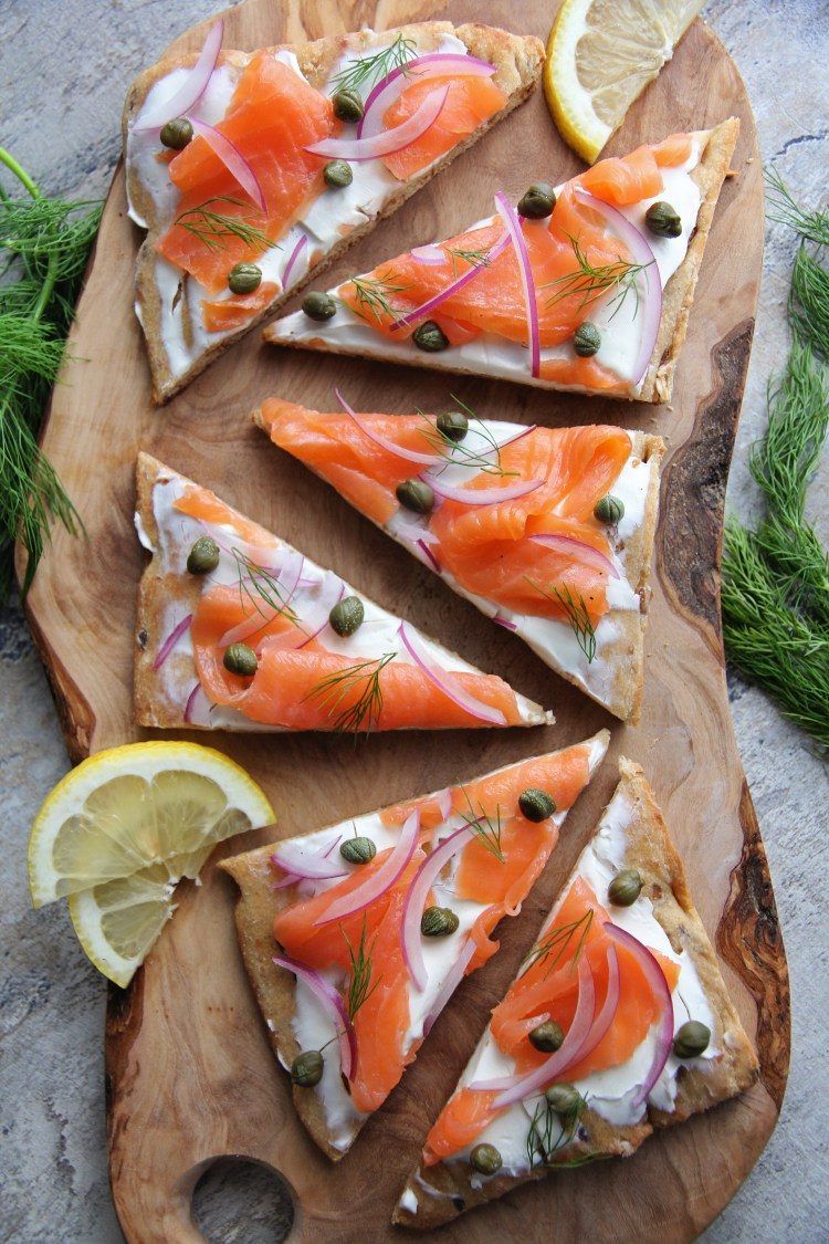 overhead image of smoked salmon flatbread cut into triangles, garnished with red onion and capers.