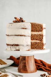 Front view of a spice cake with brown butter frosting on a cake stand, with a large slice taken out of the right side. Cake surrounded by stacked plates, orange linen and forks.