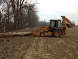 Here is our Case 580K backhoe.  This is a typical log to move from a field in the White River flood plain.  It floats out into the field, and it is our job to shove it out of the way!  At least this one can be moved mechanically.  It's the little stuff that must be picked up by hand that gives you good exercise!  This is taken at our Grubb farm location, on the south side of US 50, just west of the White River.