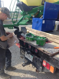 The tow halves of the transmission gearbox lie open on the back end of the service truck.  Ray is opening a package of gaskets and seals to stop the leak that had developed in that transmission.  His repair was successful!