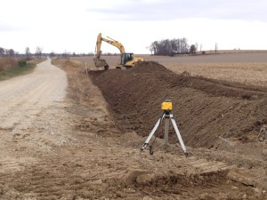 """This new channel being carved along the gravel road will re-direct the water coming from above...water will no longer flow out into this field, but remain along the road.  See the laser generator on the tripod?  Beneath that is the opening to a newly-installed 30"""" x 100' culvert that creates a new entrance to the field.  The culvert pipe creates a new field entrance."""