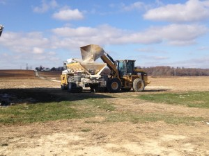 CPS folks load the variable-rate spreader from a pile of lime dumped in the field