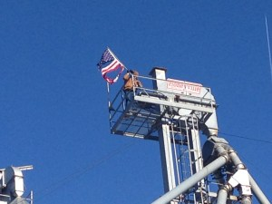 90+ feet in the air, John is replacing the flag on top of the newer elevator.  It's illuminated at night.