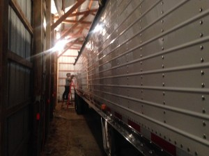 In the storage barn, Brandon polishes on the Pete's trailer
