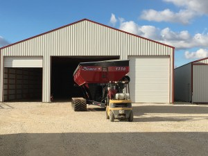 The grain cart comes out of the back of the storage building...