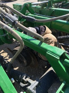 Brandon removes the worn gauge wheels, and replaces the broken seed-lock tabs.