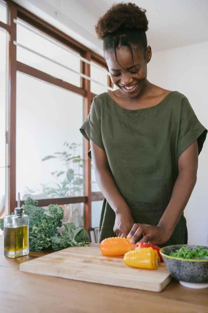 woman in green tank top holding orange bell pepper