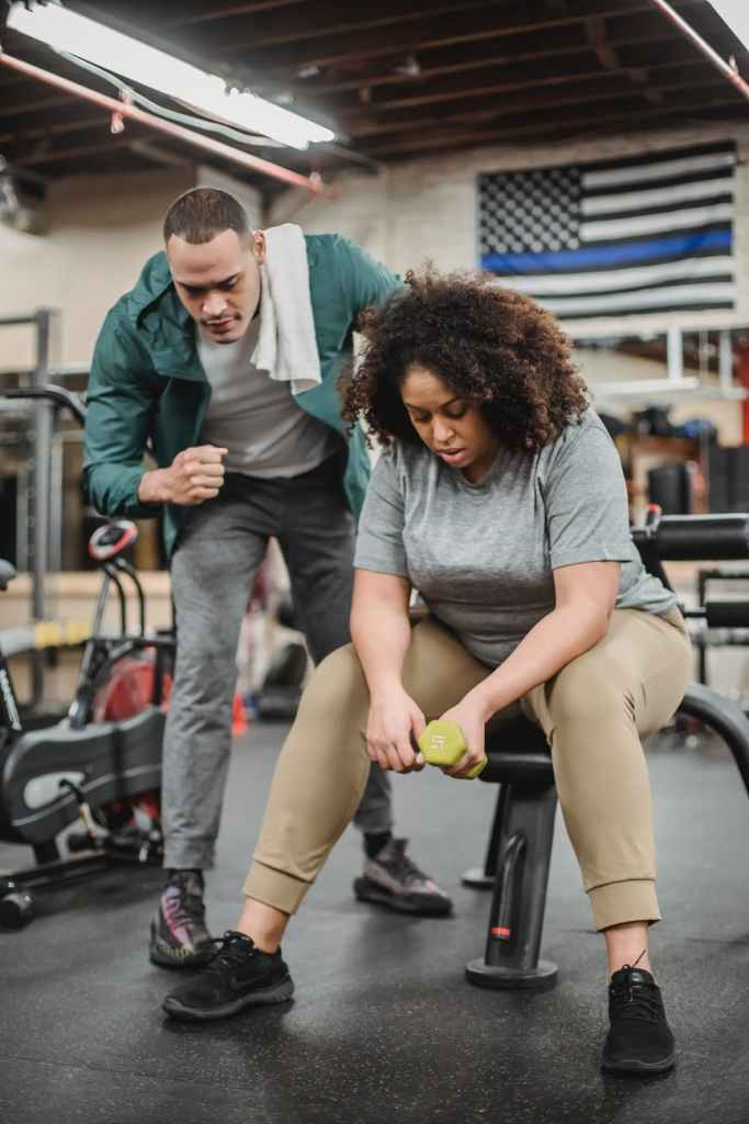 trainer helping plump woman exercising with dumbbell