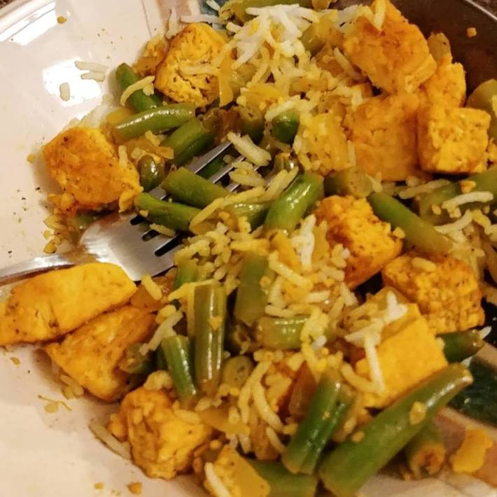 Curried tofu and green beans Indian inspired dish served with rice.