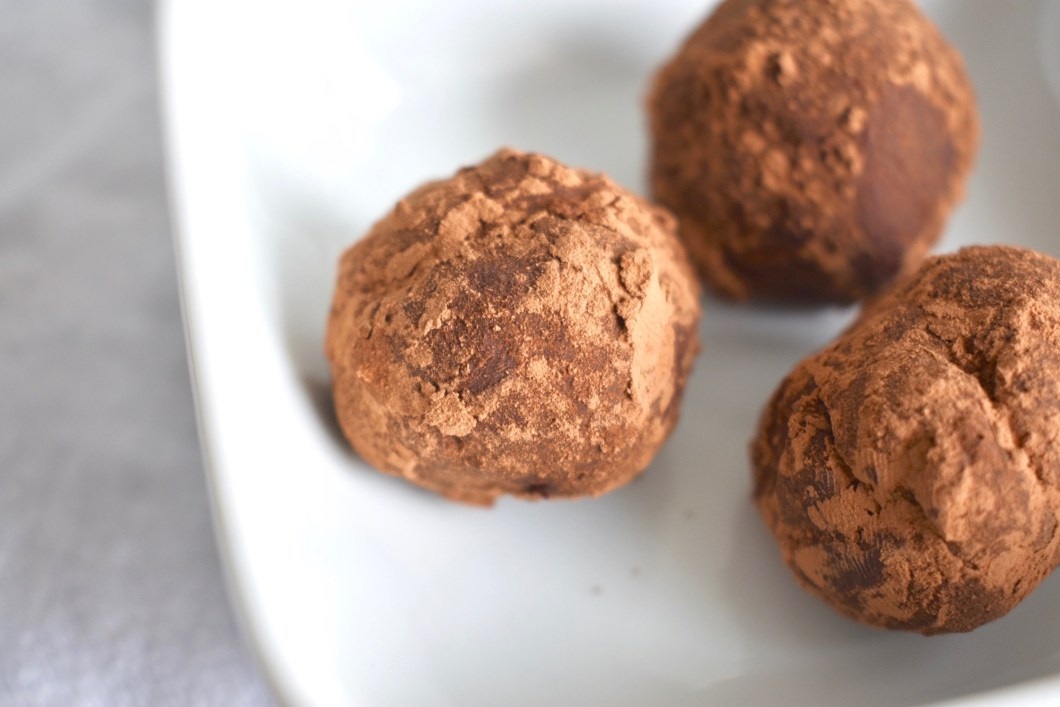 closeup photo of three chocolate truffles dusted in chocolate chili powder