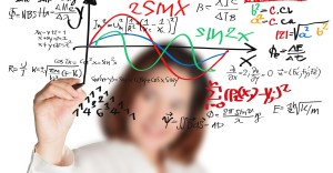 female teacher writing various high school maths and science formula
