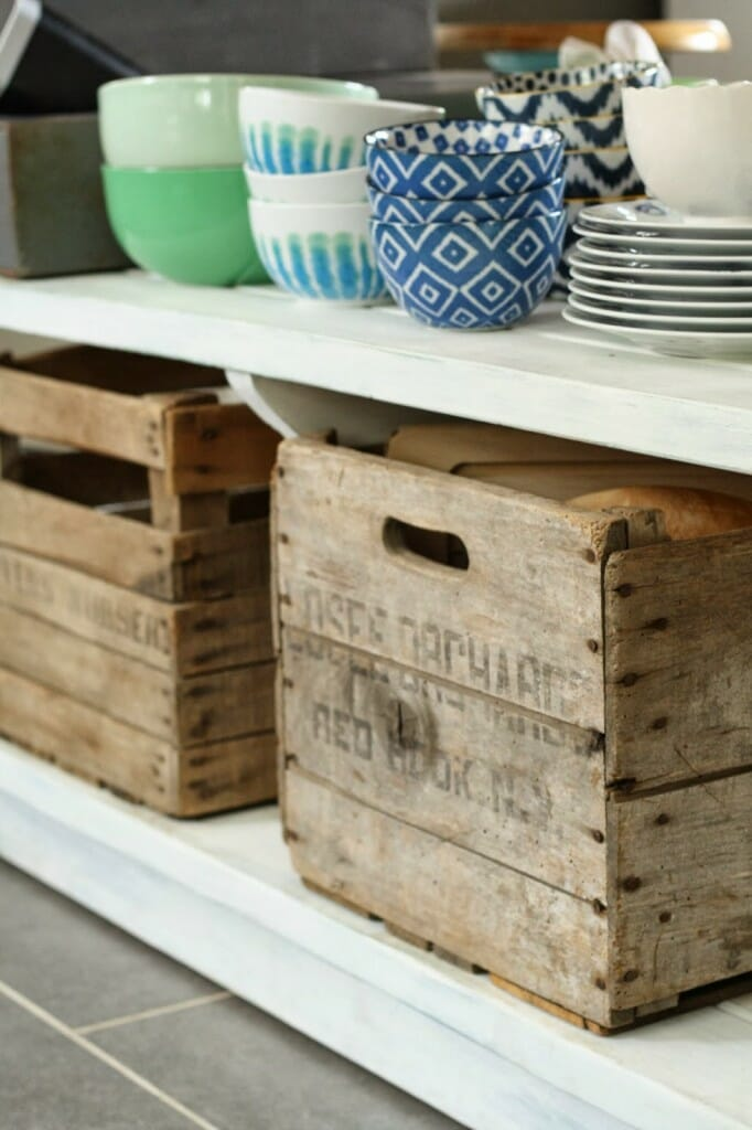open shelving on island for every day dishes and vintage crates for storage