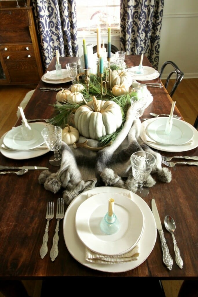 Blue & Green Thanksgiving table with a blanket, pines, and pumpkins, and message in a bottle place cards