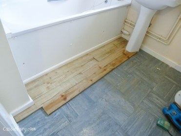 using recycled wood from a skip to make a beach hut bathroom floor and storage