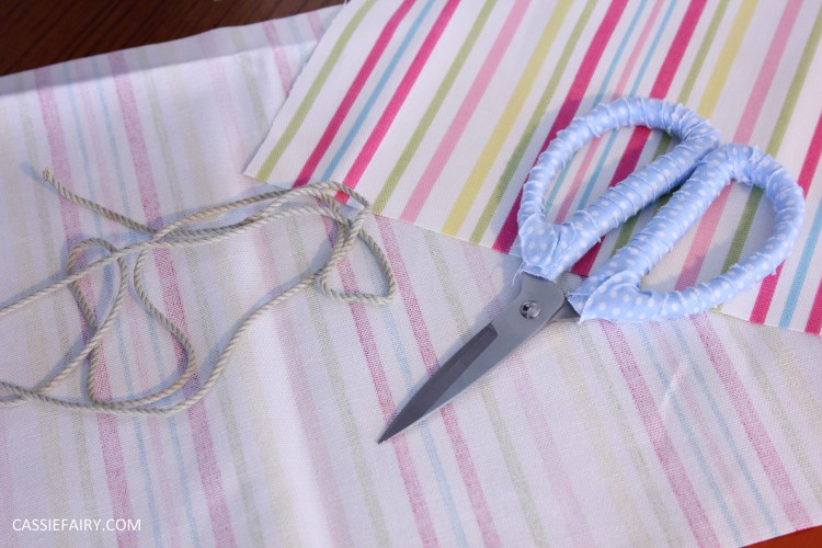 Photo of striped fabric and thread with a pair of scissors