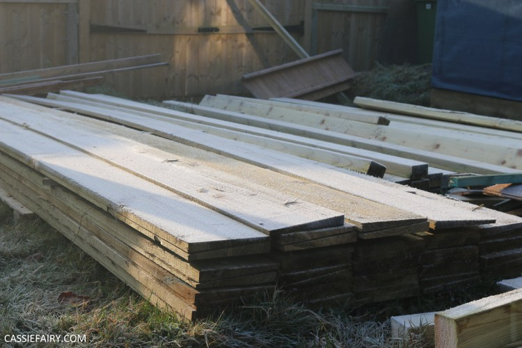 Pile of wood planks in garden, covered in frost.