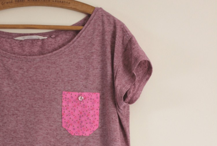 Photo of a purple t-shirt with contrasting applique pocket hanging on a coat hanger