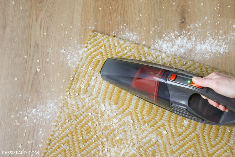 photo of handheld vacuum sucking up spilled flour off a yellow rug